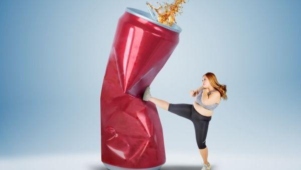 Сахарозаменители в диетических газированных напитках - девушка сминает жестяную банку ударом ногифото